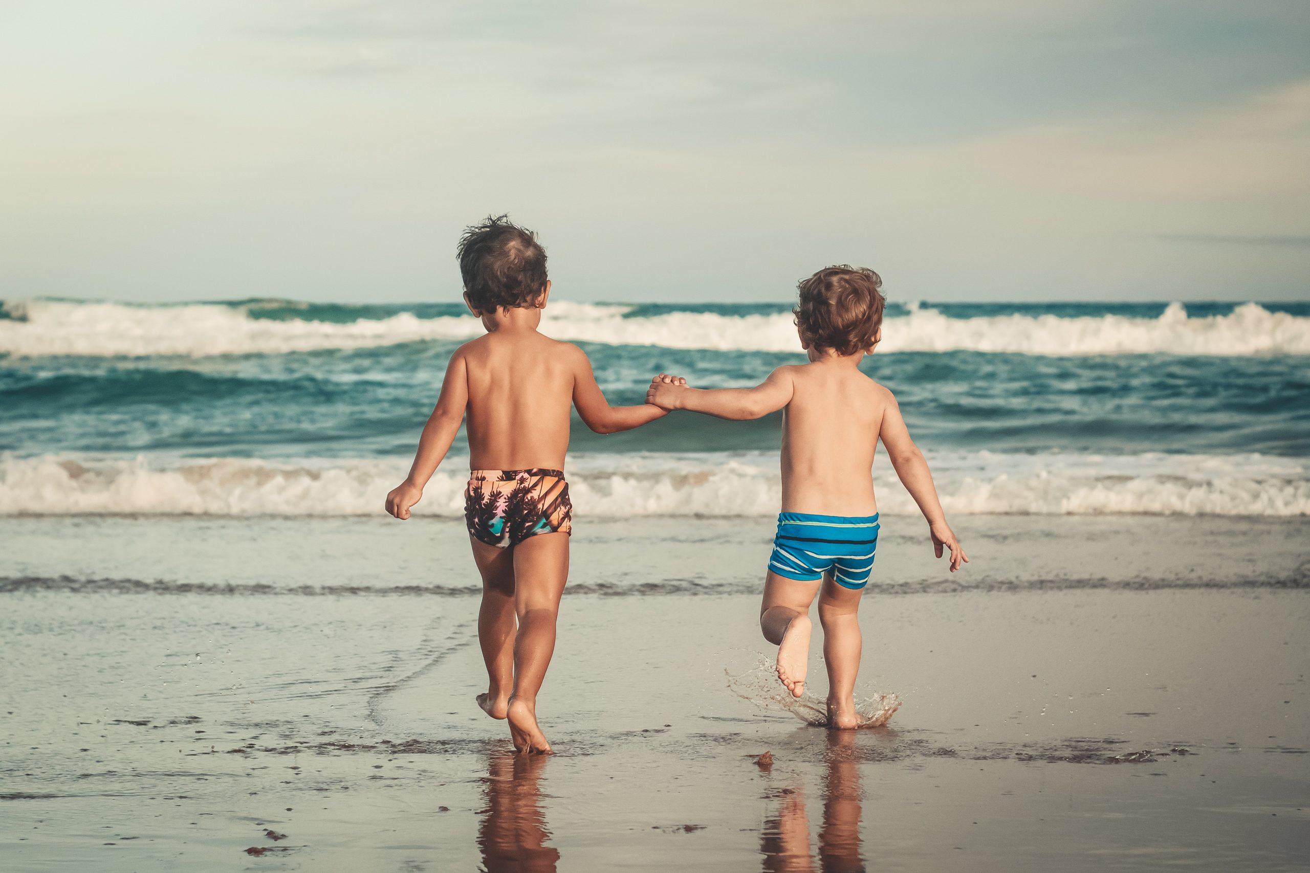 niños mano playa